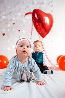 Deux enfants mignons, un garçon et une fille, en tenues posent avec des ballons rouges
