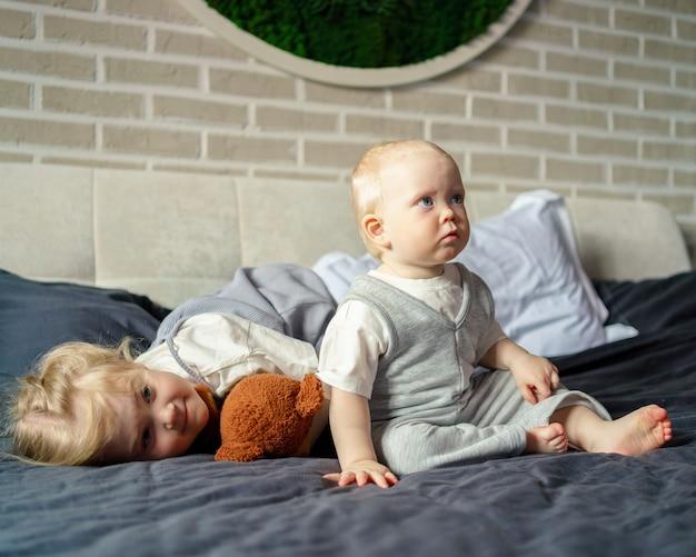 Deux enfants mignons jouant ensemble sur un grand lit à la maison