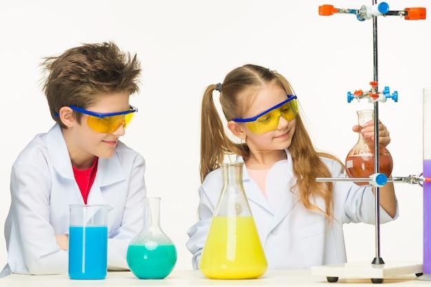 Deux enfants mignons à la leçon de chimie faisant des expériences sur fond blanc