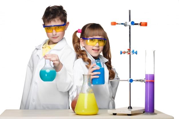Deux enfants mignons à la leçon de chimie faisant des expériences