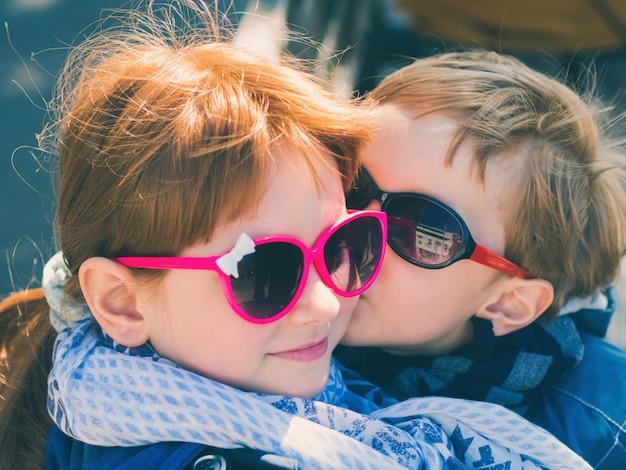 Deux enfants mignons avec des lunettes de soleil. garçon embrasser fille