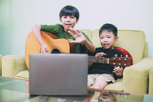 Deux enfants musiciens faisant de la diffusion en direct et montrant un geste dire bonjour au public sur un ordinateur portable
