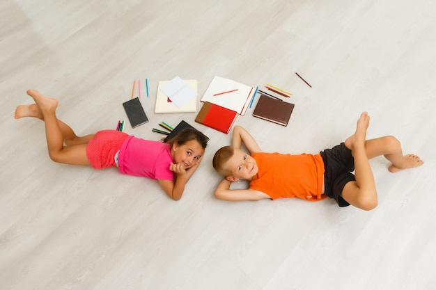 Deux enfants, petites filles d'âge préscolaire regardant une tablette à la maison à l'étage