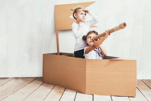 Deux enfants petites filles à la maison dans un bateau en carton jouent aux capitaines et marins