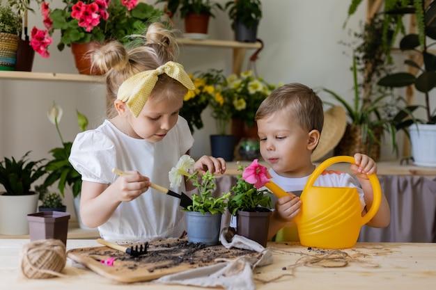 Deux enfants plantes et greffes et arrose les fleurs d'intérieur d'un arrosoir jaune