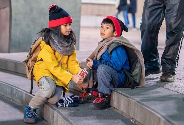 Deux enfants portant des vêtements d'hiver est assis sur un escalier
