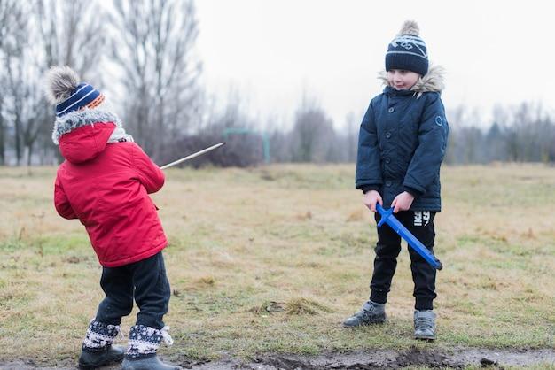 Deux enfants qui jouent dehors avec de la boue