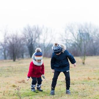 Deux enfants qui jouent dehors un jour de pluie