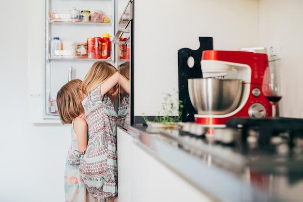 Deux enfants de sexe féminin affamés irrésistiblement faim à la recherche de nourriture dans le réfrigérateur