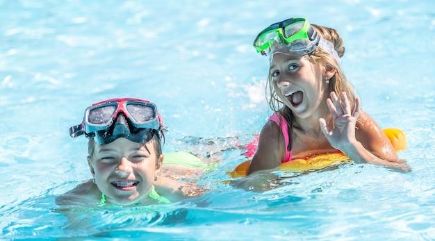 Deux enfants de sexe féminin s'amusant à l'intérieur de la piscine un jour d'été portant des lunettes de natation sur le front.