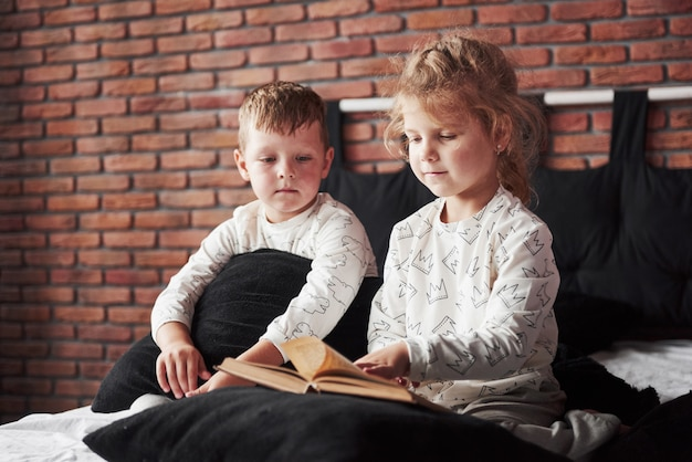 Deux enfants sont allongés sur un grand lit et lisent un livre intéressant. ils sont vêtus du même pyjama