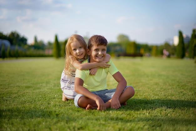 Deux enfants souriants heureux posant assis sur l'herbe verte.