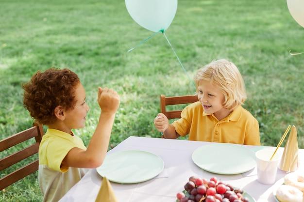 Deux enfants à la table de pique-nique à l'extérieur décorés de ballons pour la fête d'anniversaire dans l'espace de copie d'été