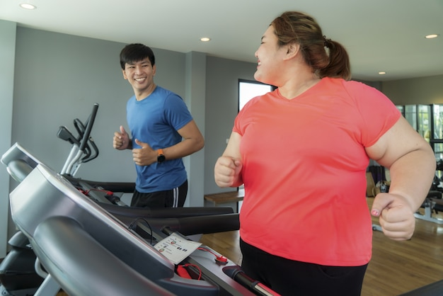 Deux entraîneur asiatique et femme en surpoids exerçant une formation sur tapis roulant dans une salle de sport, entraîneur thump up