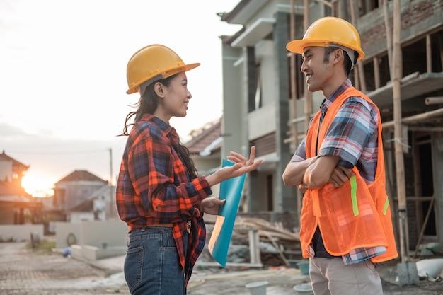 Deux entrepreneurs asiatiques discutant avec des gestes de la main dans le contexte d'un bâtiment inachevé