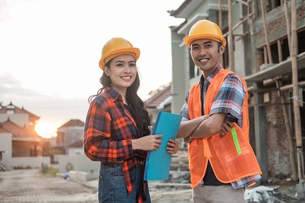Deux entrepreneurs asiatiques portant des casques et des gilets de sécurité dans le contexte d'un bâtiment inachevé