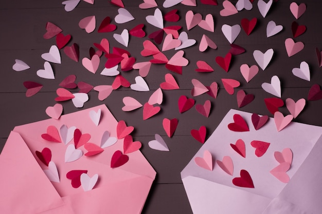 Deux enveloppes avec des coeurs en papier sur bois gris