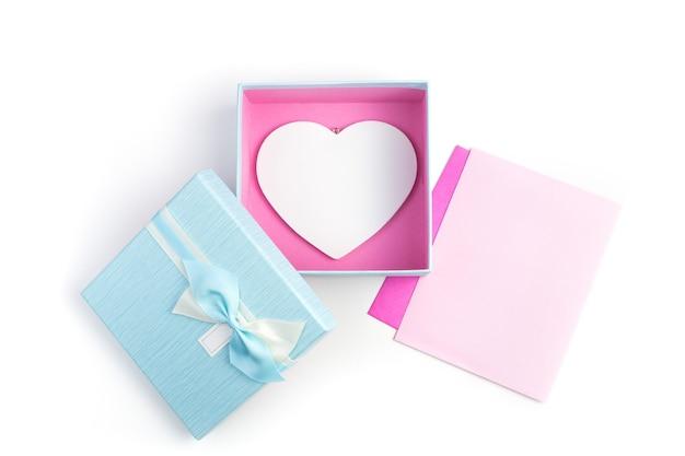 Deux enveloppes et un coffret cadeau avec un cœur sur fond clair.