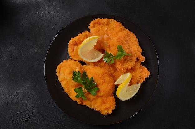 Deux escalopes de poulet panées au citron sur une assiette