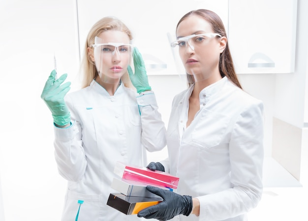 Deux esthéticiennes posent dans un cabinet médical avec des préparations cosmétiques et une seringue. concept de rajeunissement de la peau. technique mixte