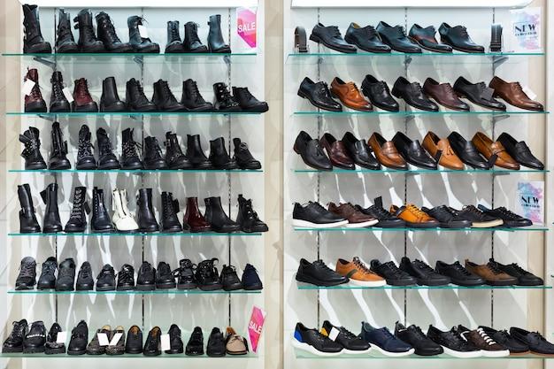 Deux étagères en verre avec des chaussures d'homme dans un magasin