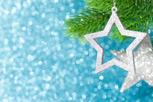 Deux étoiles d'argent sur une branche d'arbre de noël sur un fond bleu brillant de bokeh.