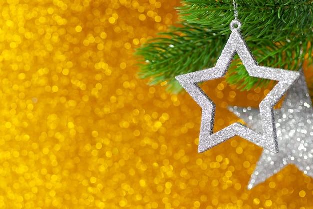 Deux étoiles d'argent sur une branche d'arbre de noël sur un fond jaune brillant de bokeh