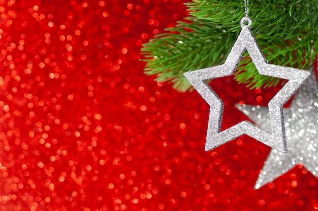 Deux étoiles d'argent sur une branche d'arbre de noël sur un fond rouge brillant de bokeh