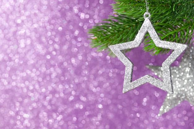 Deux étoiles d'argent sur une branche d'arbre de noël sur un fond violet brillant de bokeh