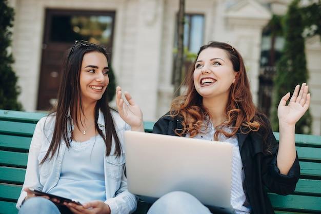 Deux étonnantes femme caucasienne s'amusant assis sur un banc contre un bâtiment en riant tout en tenant un ordinateur portable sur les jambes.