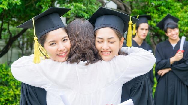 Deux étudiantes asiatiques avec les robes de graduation câlin parent