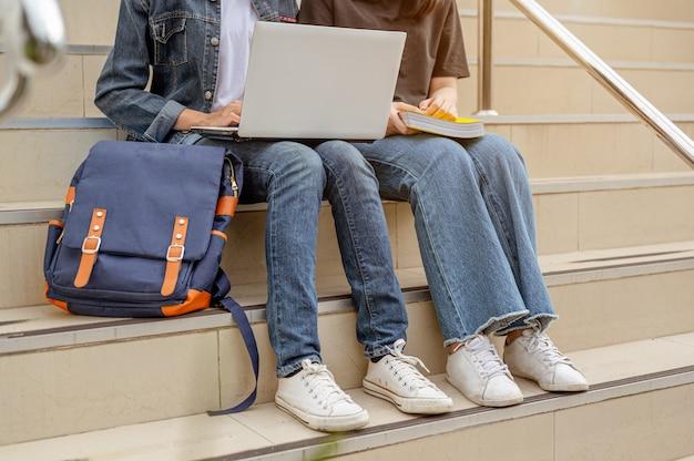 Deux étudiantes asiatiques s'assoient dans les escaliers et utilisent leur ordinateur portable pour aller à l'université