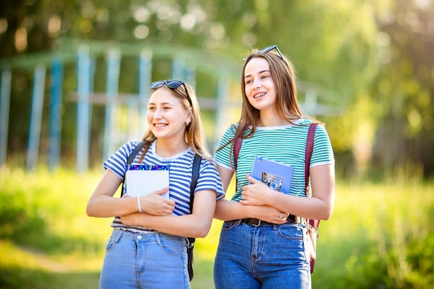 Deux étudiantes heureuses marchant et se parlant dans un campus au coucher du soleil avec une lumière chaude.