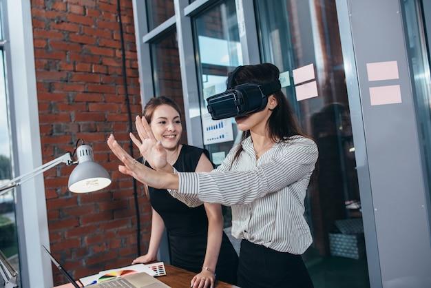 Deux étudiantes jouant à un jeu 3d dans des lunettes vr ayant une pause après une leçon en classe.