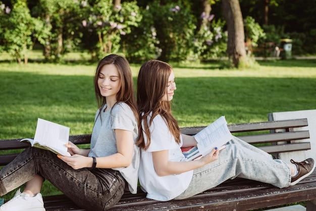 Deux étudiantes regardent un livre ouvert sur un banc dans le parc. enseignement à distance, préparation aux examens. mise au point sélective douce.
