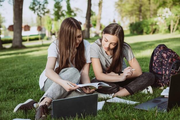 Deux étudiantes sont assises dans le parc sur l'herbe avec des livres et des ordinateurs portables, étudient et se préparent aux examens. l'enseignement à distance. mise au point sélective douce.