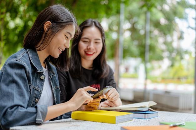 Deux étudiantes utilisaient un téléphone pour trouver des informations sur leurs études livres de connaissances