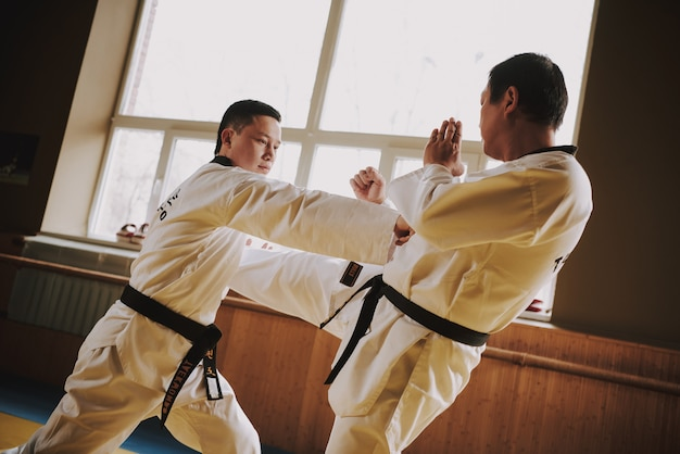 Deux étudiants d'arts martiaux en blanc sparring ensemble.