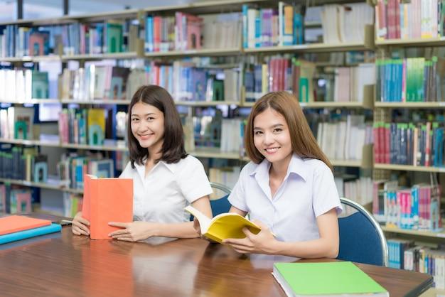 Deux étudiants asiatiques étudient ensemble dans la bibliothèque à l'université.