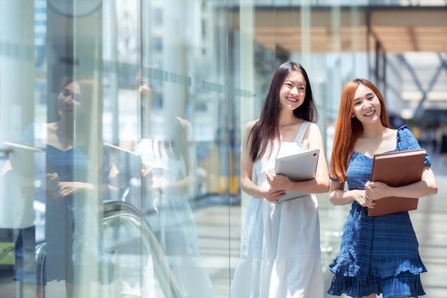Deux étudiants asiatiques marchant vers la bibliothèque dans son université