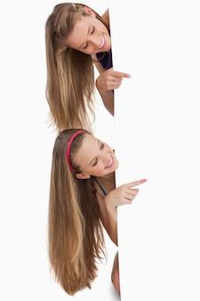 Deux étudiants en cheveux longs pointant derrière une pancarte blanche
