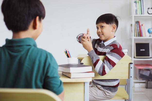 Deux étudiants heureux s'amusant et jouant dans une salle de classe