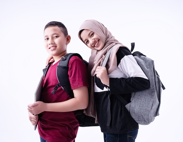 Deux étudiants musulmans debout ensemble, sur fond blanc, avec le sourire et le sentiment heureux