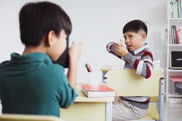 Deux étudiants s'amusant et jouant à la fusillade en classe