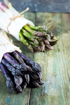 Deux faisceaux organiques frais et naturels de légumes asperges vertes et violettes sur un fond en bois.