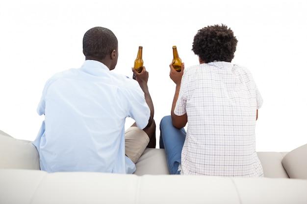 Deux fans de sport assis sur le canapé avec des bières
