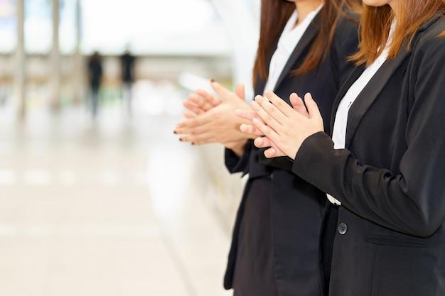 Deux femme d'affaires, frappant des mains en se tenant debout pour le concept de félicitation.