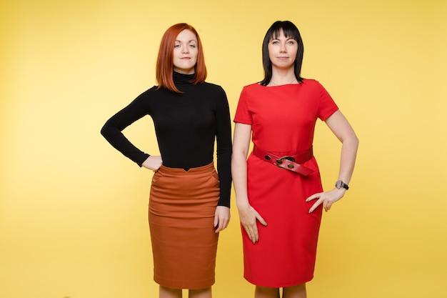Deux femme d'affaires souriante et confiante posant en regardant la caméra. mode élégante jeune femme debout isolé sur fond jaune ayant une émotion positive