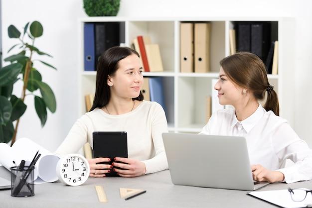 Deux, femme affaires, tenue, tablette numérique, et, ordinateur portable, regarder, autre