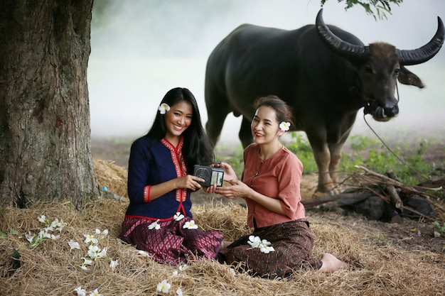 Deux femme asiatique portant un costume traditionnel thaïlandais assis dans le champ, tout en écoutant la radio de style vintage à côté de buffalo